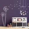 The Freya dandelion wall decal in light grey vinyl over a crib  in a nursery room.