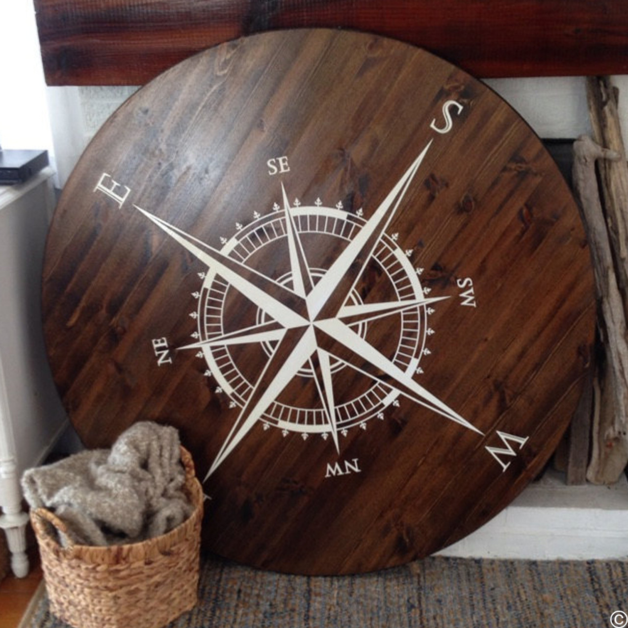 Customer photo of The Explorer Compass wall or ceiling decal shown here in white vinyl on a table top. With this type of install, add a top coat of polyurethane to seal and protect your compass design from drinks and table use.