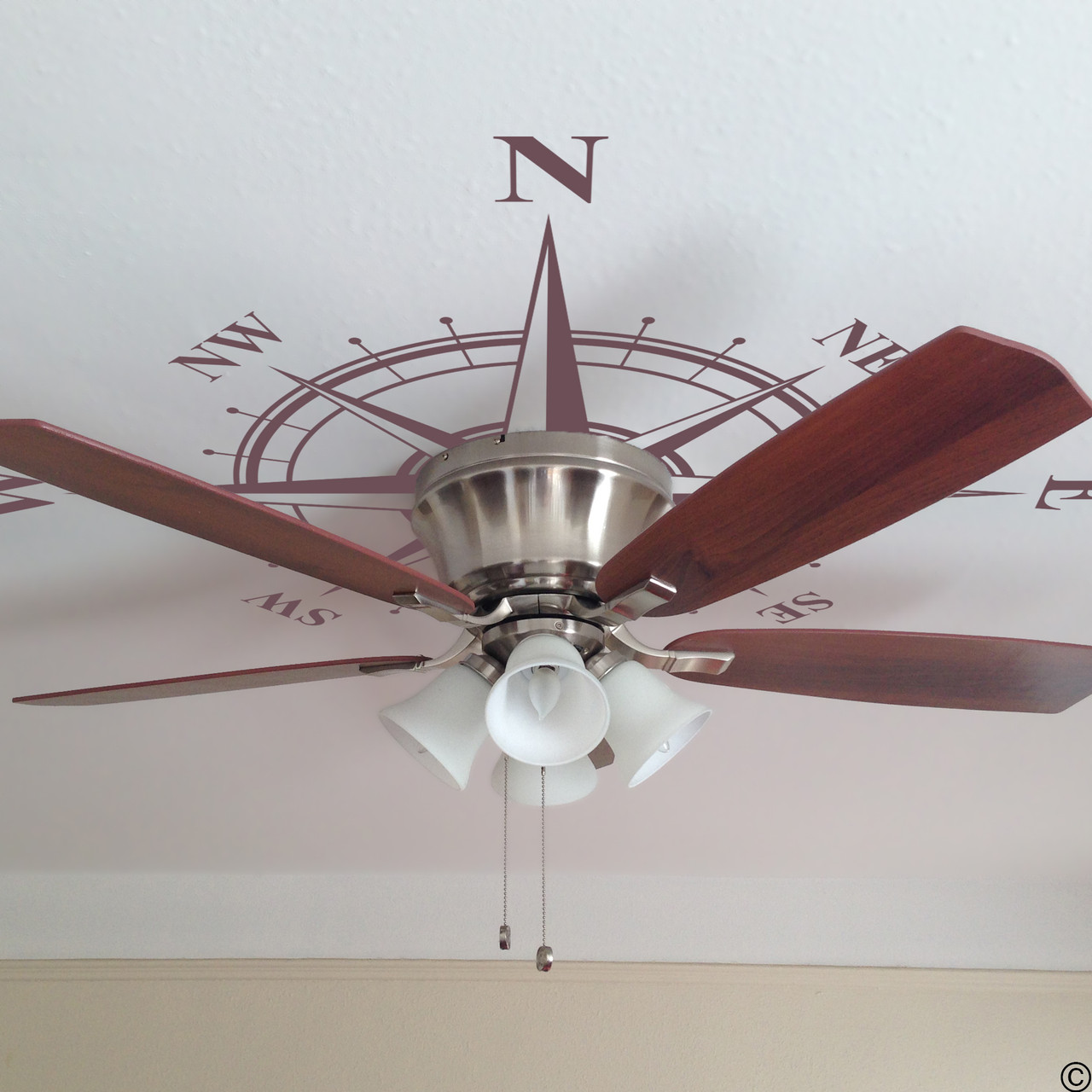 The Charles compass wall decal shown here on a ceiling and placed under a ceiling fan in limited edition eggplant vinyl.
