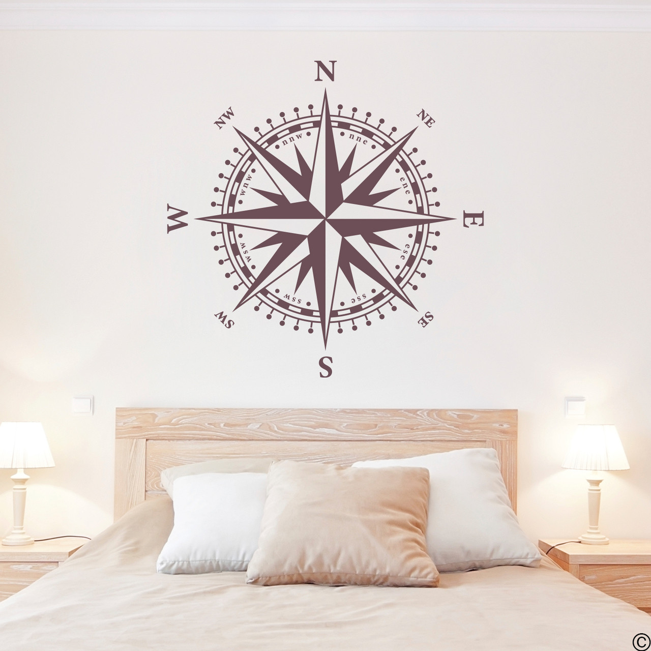The Christopher Compass wall decal in eggplant vinyl and placed over a headboard in a bedroom.