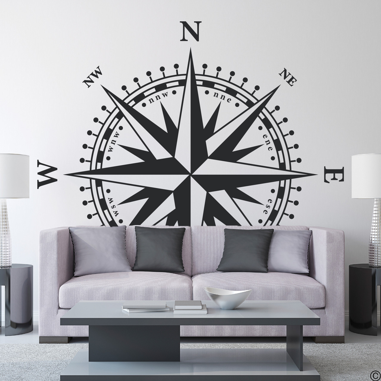 The Christopher Compass wall decal in black vinyl and placed over a couch in a living room.