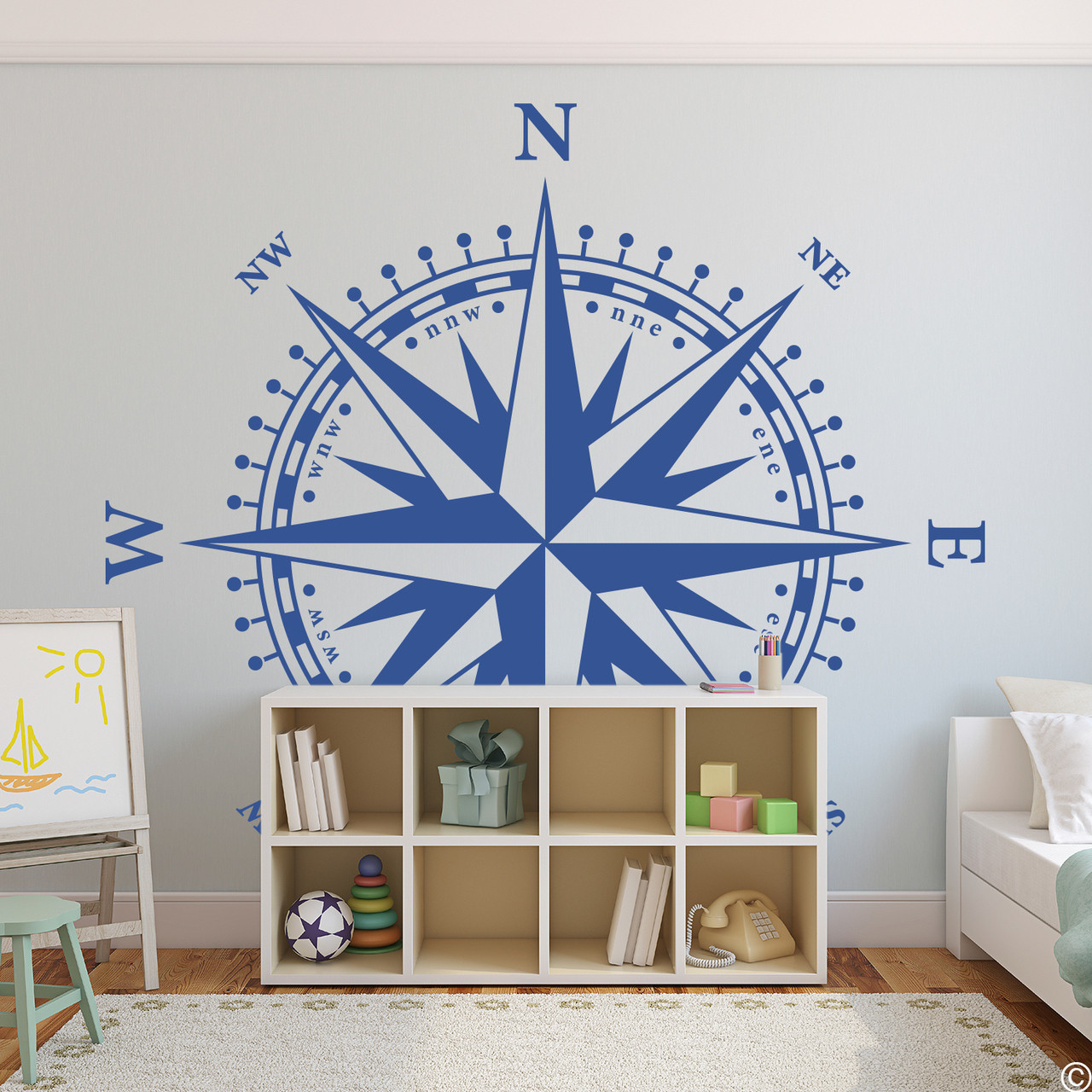 The Christopher Compass wall decal in denim vinyl and placed over a short shelve in a kids room.