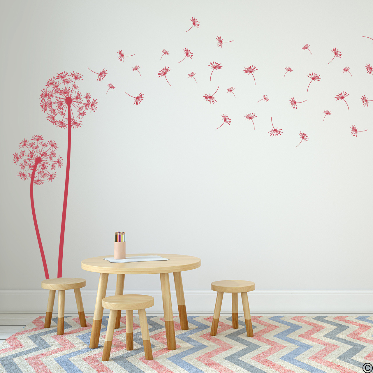 The Freya dandelion wall decal in dahlia red vinyl and placed in a kids playroom.
