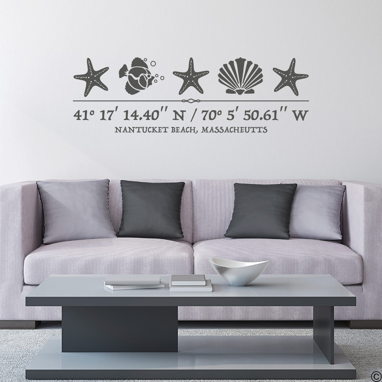Sea Life wall decal, includes three starfish, one shell, one fish, and customizable GPS coordinates with town and state name. Shown here in dark grey vinyl and on a wall above a couch.