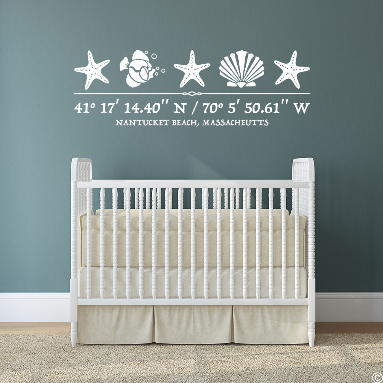 Sea Life wall decal, includes three starfish, one shell, one fish, and customizable GPS coordinates with town and state name. Shown here in white vinyl and on a nursery wall above a crib.