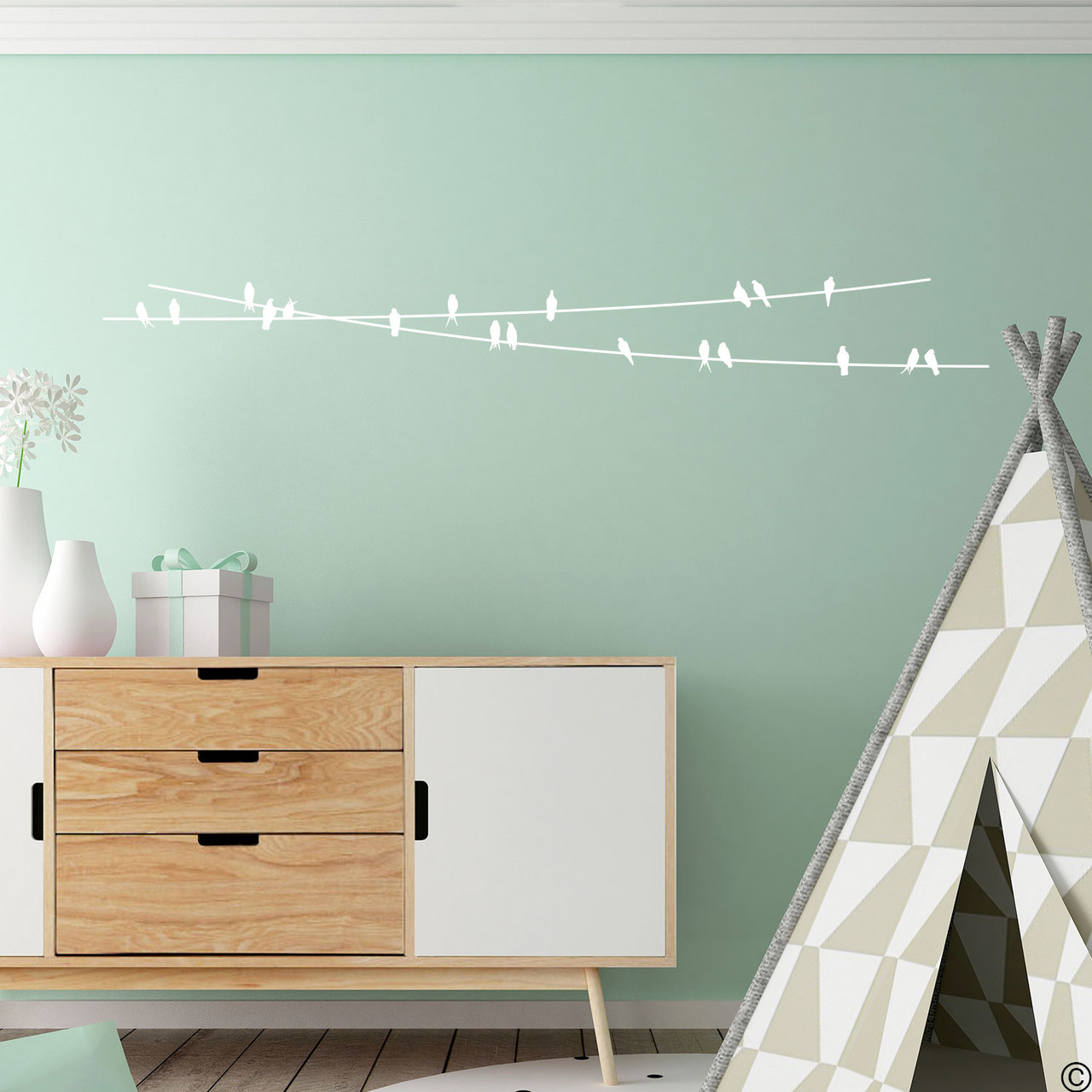 """The """"Birds On Wire"""" wall decal placed in a playroom in white vinyl color."""