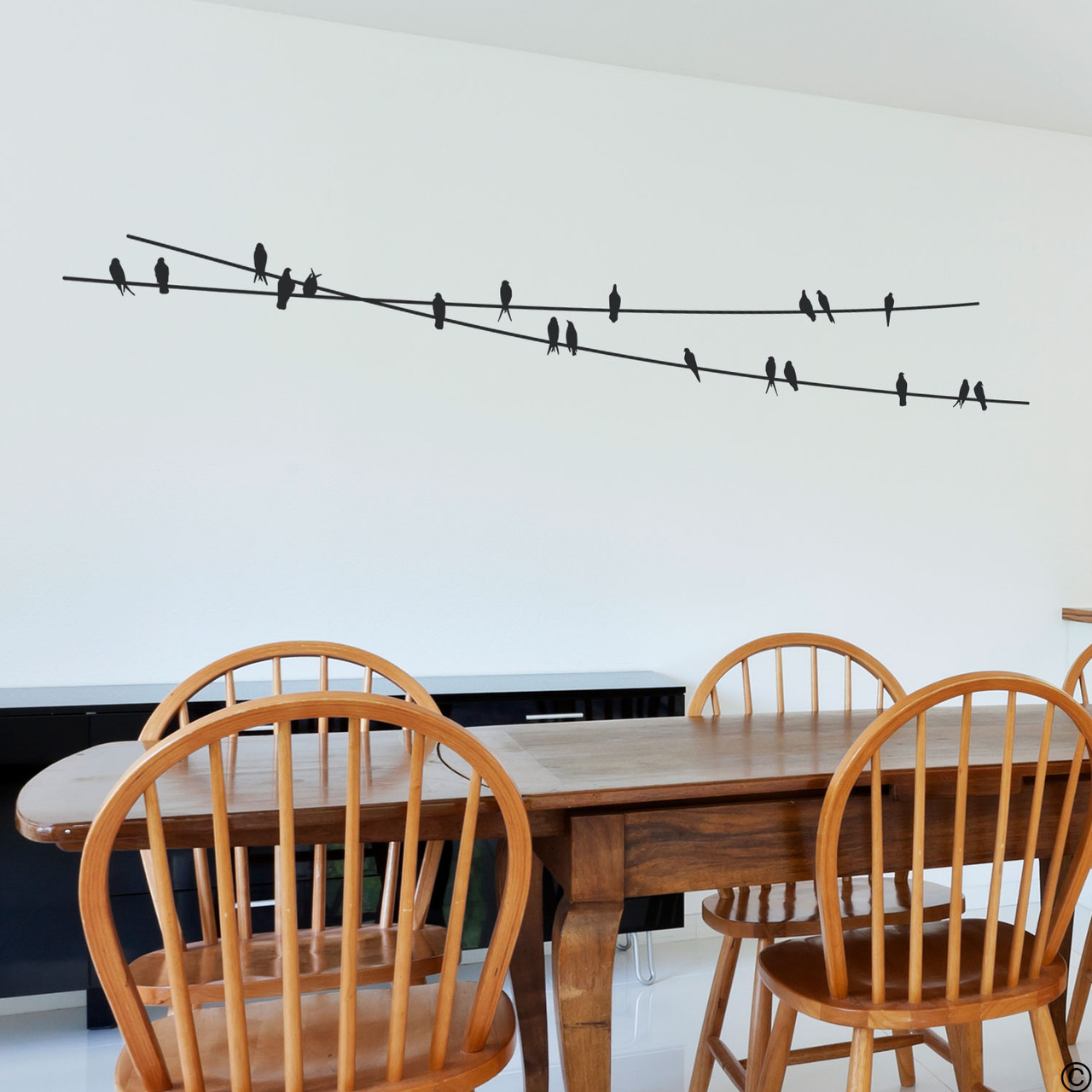 """The """"Birds On Wire"""" wall decal placed above a kitchen table in black vinyl color."""