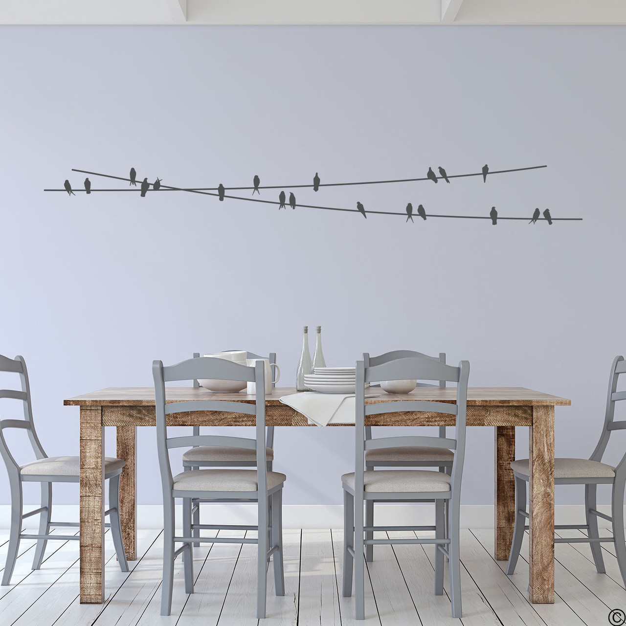 """The """"Birds On Wire"""" wall decal placed above a kitchen table in dark grey vinyl color."""