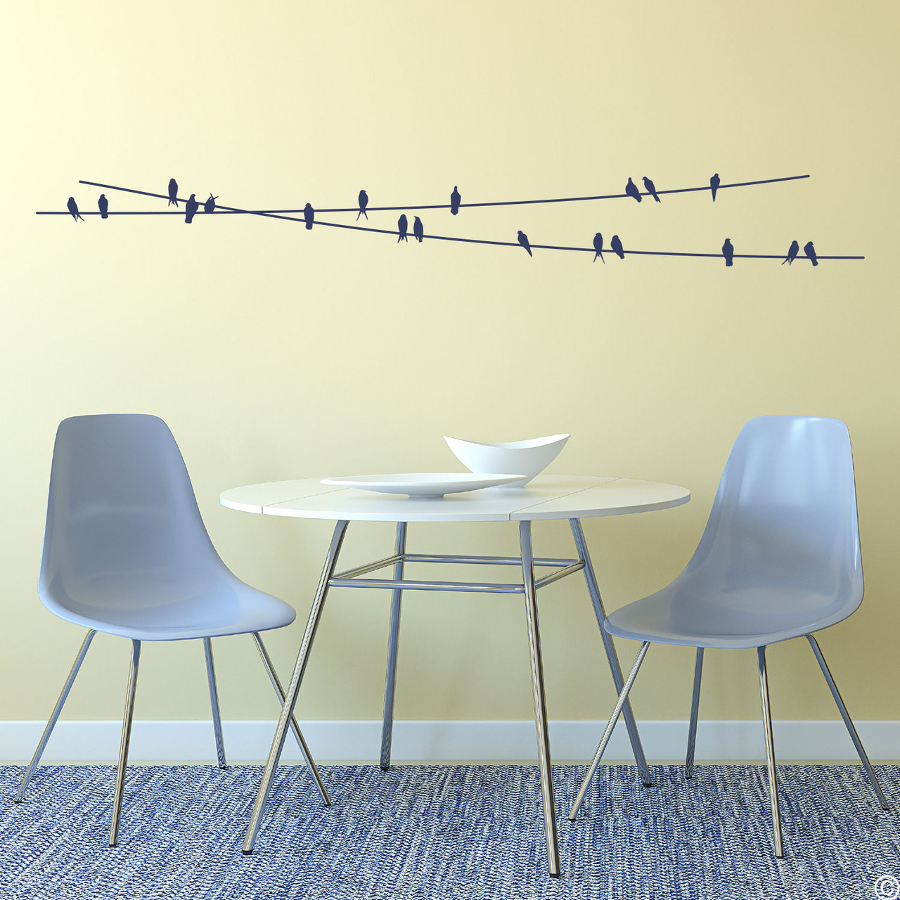 """The """"Birds On Wire"""" wall decal placed above a kitchen table in dark blue vinyl color."""