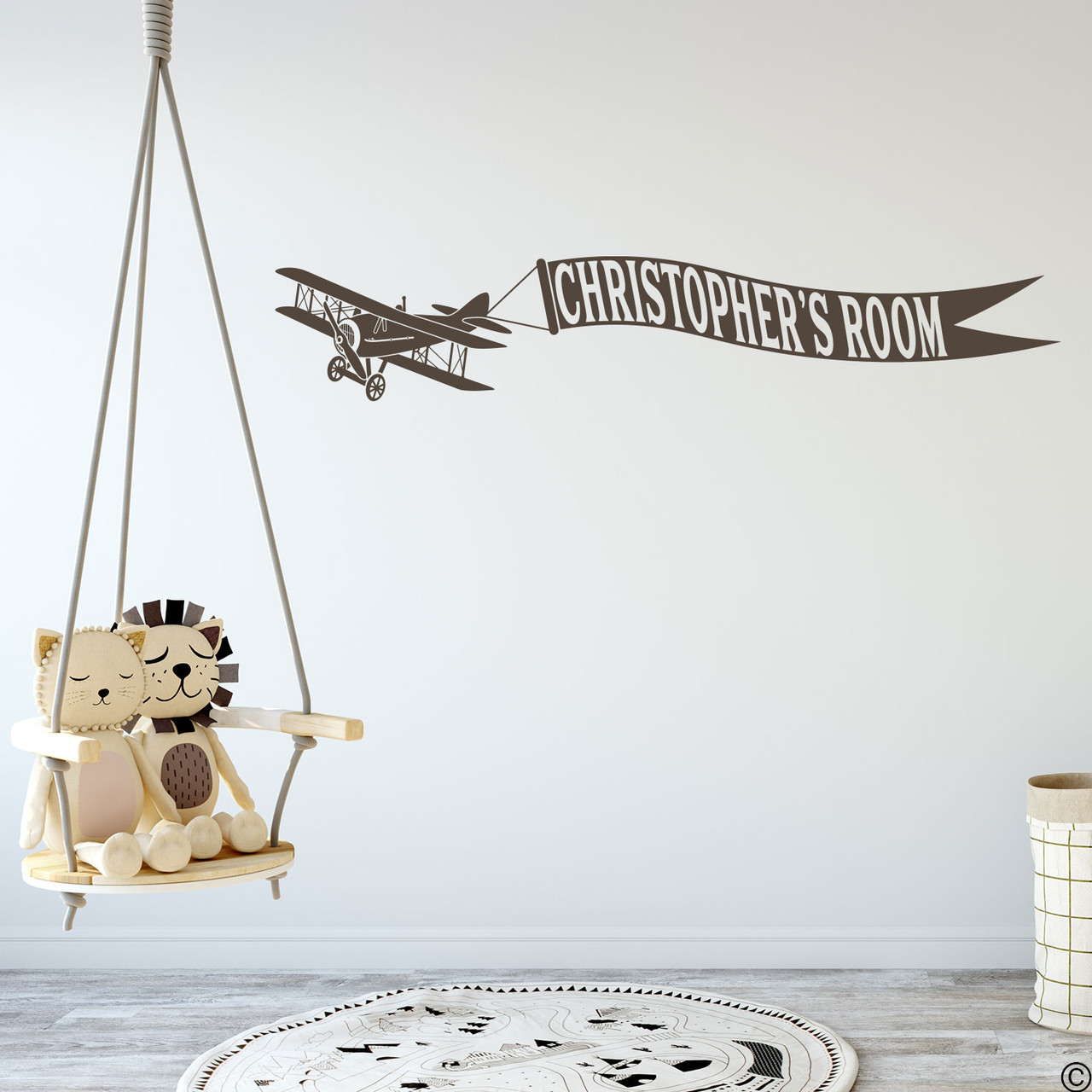 Biplane wall decal with customizable name banner on a kids playroom wall in brown vinyl.
