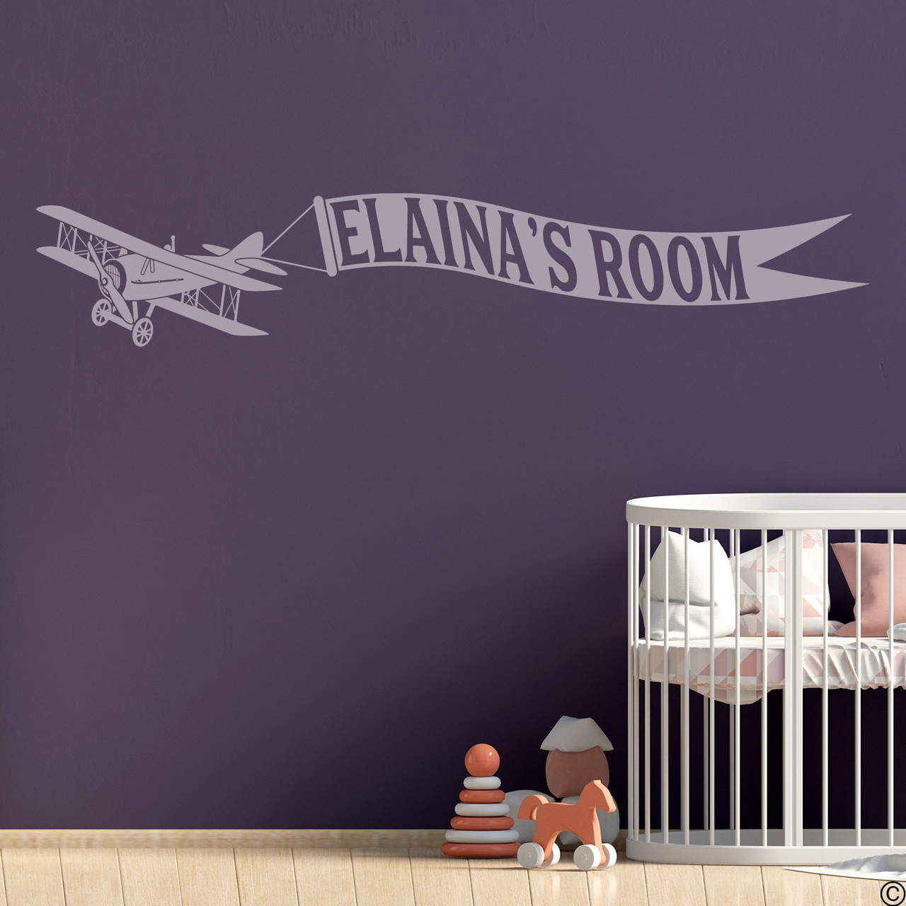 Biplane wall decal with customizable name banner on a nursery room wall in limited edition wisteria vinyl.