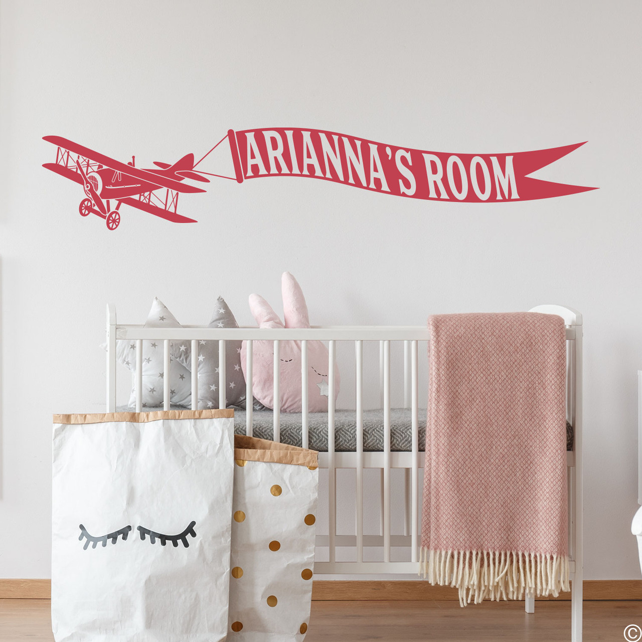 Biplane wall decal with customizable name banner on a nursery room wall in dahlia red vinyl.