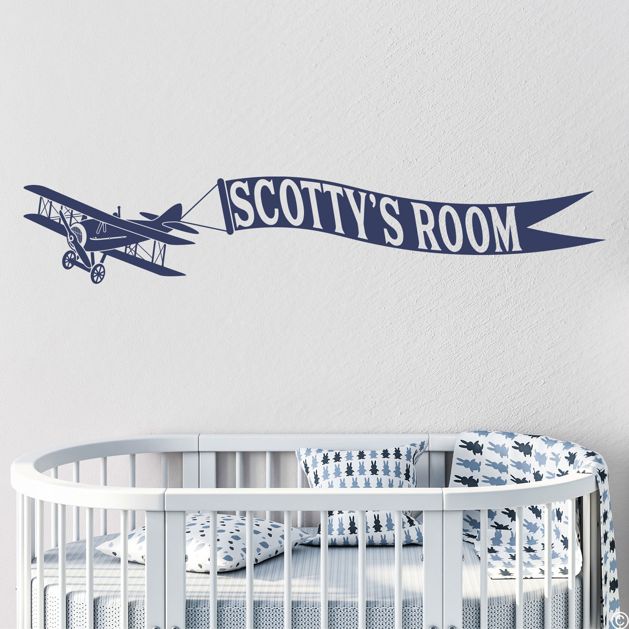 Biplane wall decal with customizable name banner on a nursery room wall in dark blue vinyl.