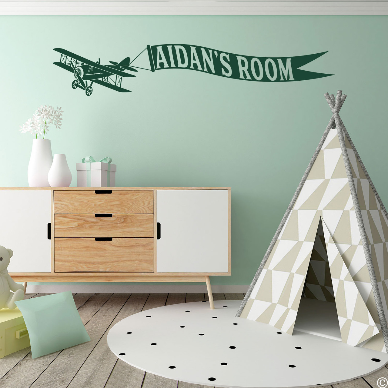 Biplane wall decal with customizable name banner on a kids playroom wall in dark green vinyl.
