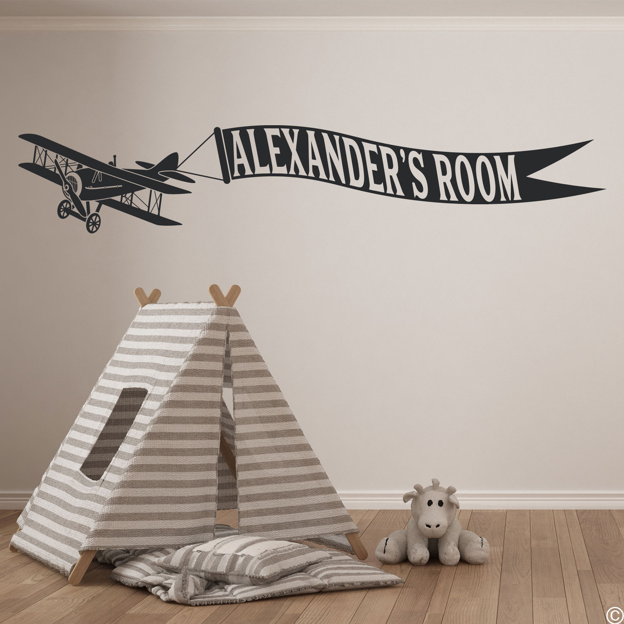 Biplane wall decal with customizable name banner on a kids playroom wall in black vinyl.