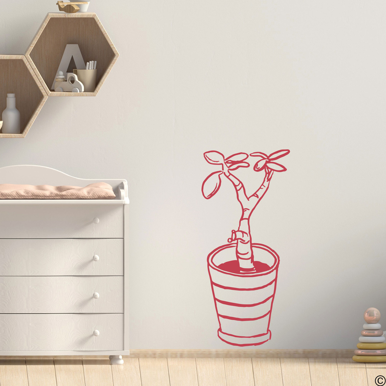 The hand drawn baby jade potted plant wall decal in the dahlia red vinyl color.