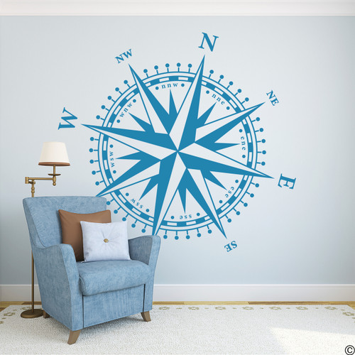 The Christopher Compass wall decal in bayou blue vinyl and placed beside a chair in a living room.
