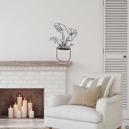 The hand drawn Swiss cheese potted plant wall decal on a fireplace mantle in black vinyl.