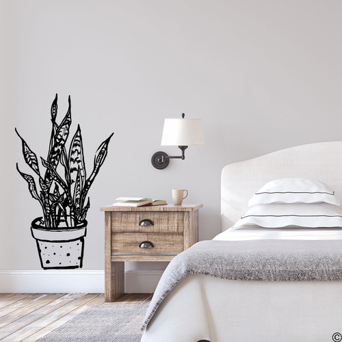 The hand drawn snake plant with polka dot pot wall decal in black vinyl.