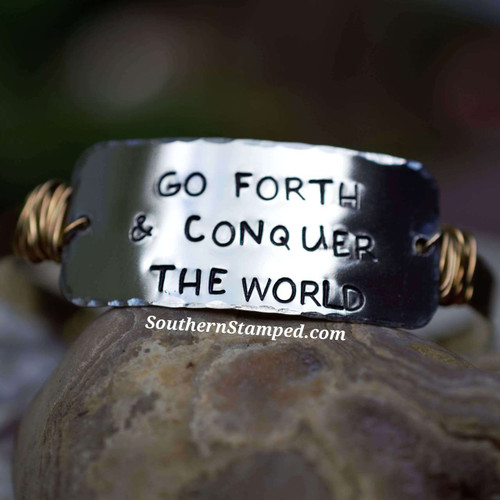 Go forth and conquer the world silver wide bar with brass wire wrapping on a brass cuff bracelet