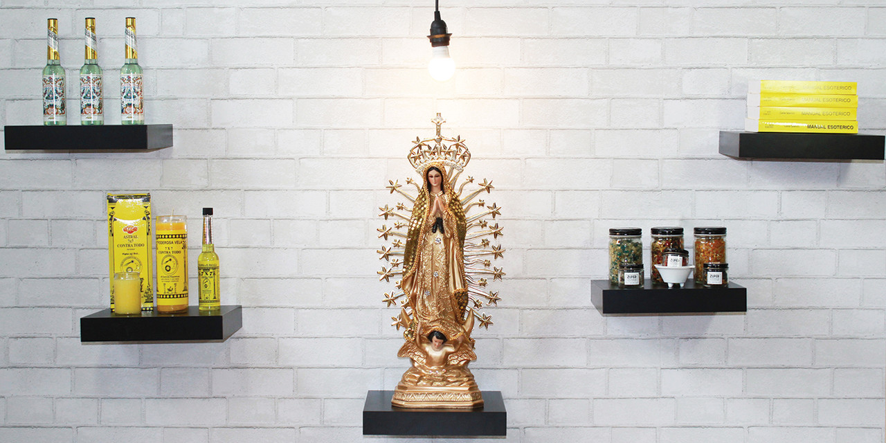 Botanica Florida water products, 7x7 Contra Todo Products, Manual Esoterico book, Zuperstitious Incense and Gold Vigen of Guadalupe displayed in a white brick wall, black shelves and lightbulb, santeria religious goods.