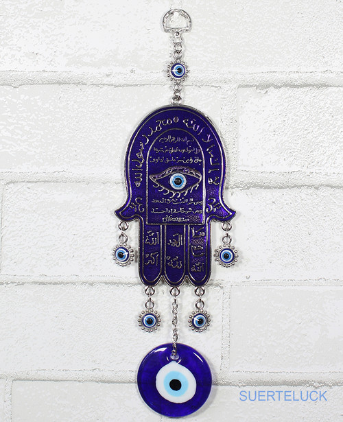 7 Spinning Evil Eyes with Hamsa Hand Hanging From a White Brick Wall.  Navy blue color