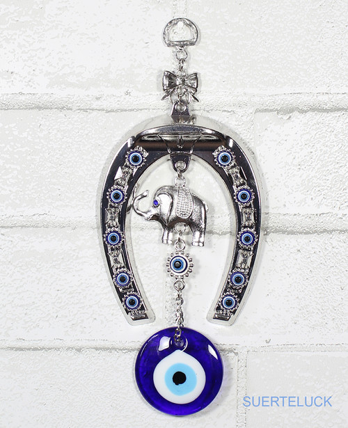 Spinning Horseshoe and Elephant with 12 Evil Eyes hanging from a white brick wall.