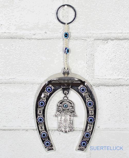 Braided Evil Eye Hamsa Hand and Horseshoe hung from a white brick wall.