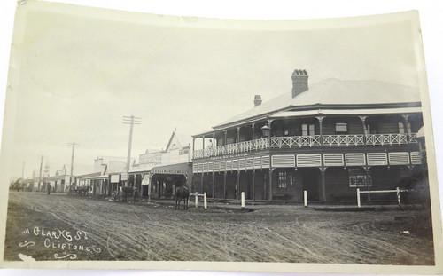 "RARE c1910 REAL PHOTO POSTCARD ""CLARKE ST, CLIFTON QLD"". HOTEL, EDELLWOOD JEWELLER, TAILOR"