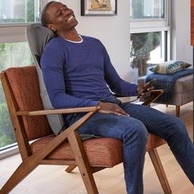 man sitting in massage cushion