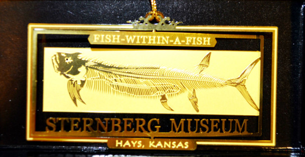 "Gold-colored metallic ornament featuring cut out image of the world-famous ""Fish-within-a-fish"" fossil."