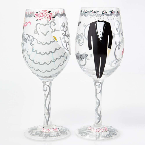 Raise a toast to celebrate your favorite couple's big day with this 15oz. Bride and Groom wine glass set. Arrives in a beautiful gift box, with a unique cocktail recipe painted under the base of the glass.
