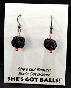 "Each pair of black leather balls consists woven leather on French wires, handcrafted especially for The Northwoods Goldsmith in the Netherlands, and are  accompanied by our delightfully tacky packaging.  Our balls come mounted on this card, with the inscription ""She's Got Beauty! She's Got Brains! She's Got Balls!"""