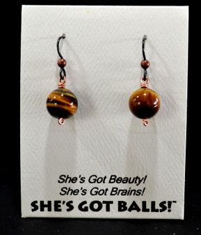 "Each pair of tiger eye balls consists of genuine tiger eye stones on French wires, accompanied by our delightfully tacky packaging. Our balls come mounted on this card, with the inscription ""She's Got Beauty! She's Got Brains! She's Got Balls!"""