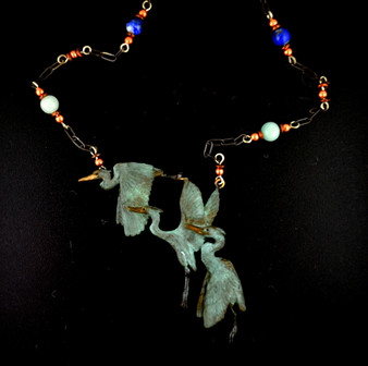 A heron is captured in three separate poses as it rises into full flight. Copper, heishi, lapis lazuli and amazonite beads decorate the 18 inch antiqued silver chain with a toggle clasp. The three herons are 2¾ inches wide by 2¼ inches high,cast in lightweight artist's bronze. Casting was created from one of Cavin's original shed-elk antler or woolly mammoth ivory carvings, to give the finished product more natural detail than is possible with a wax carving. Cast in the USA and hand finished in Washington State.