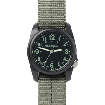 This Bertucci DX3 Plus Watch features unmatched performance and value. With classic Bertucci styling and a rugged design, this affordable field watch has a poly resin and fiber body with a stainless-steel crown and back, artistically sculpted and water resistant to 150 feet.  Beautifully designed in the heart of Chicago, every Bertucci watch is perfect for any occasion whether it's a hunting or trip in the Northwoods or an elegant dinner engagement. Black dial with drab numerals, drab band with black striping. Three year warranty. #11040