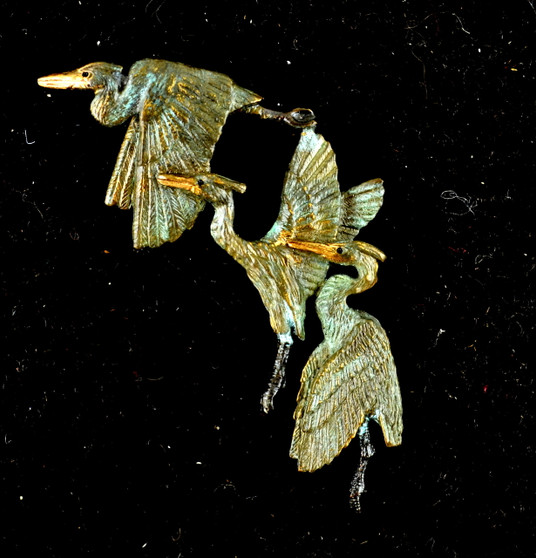 """Cavin Richie design three herons pin, cast in lightweight artist's bronze, 1.8 X 1.8"""".  Herons are shown in standing, rising, and flying positions. Casting was created from one of Cavin's original shed-elk antler or  woolly mammoth ivory carvings, to give the finished product more natural detail than is possible with a wax carving. Cast in the USA and hand finished in Washington State."""