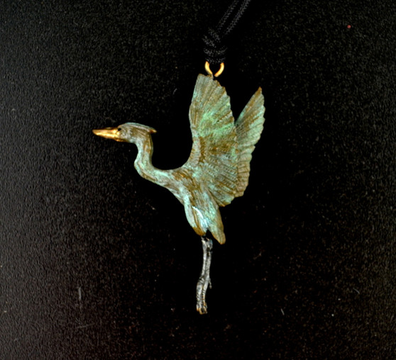 """With a wingspan of nearly six feet, the power of a rising great blue heron comes to life in this Cavin Richie design, cast in lightweight artist's bronze, 1.9"""" X 1.5"""". The fabric cord is adjustable from 18 to 36 inches. Casting was created from one of Cavin's original shed-elk antler or  woolly mammoth ivory carvings, to give the finished product more natural detail than is possible with a wax carving. Cast in the USA and hand finished in Washington State."""