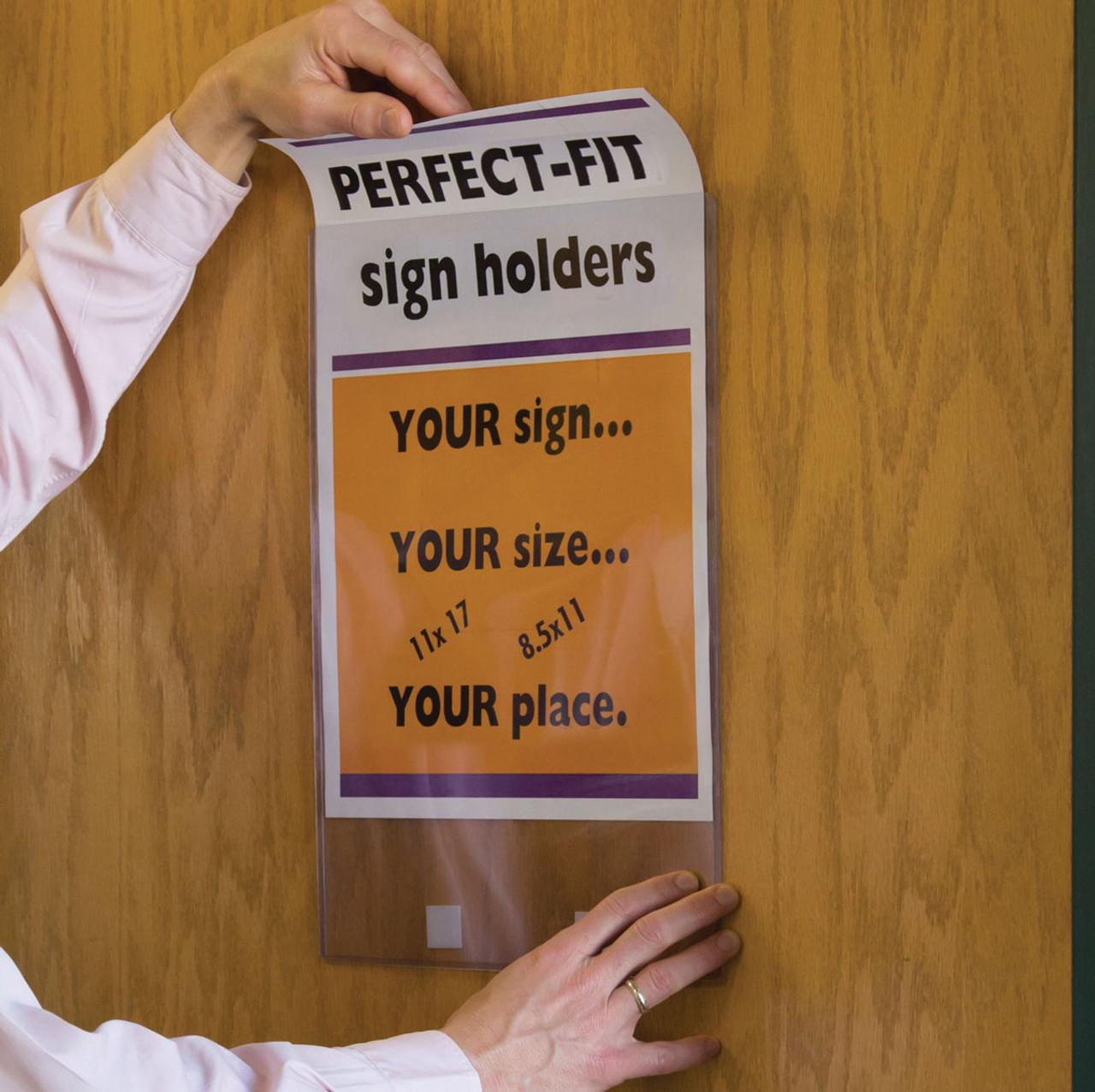 Hand sliding poster into 11x17 DocU-Sleeve on wooden office door