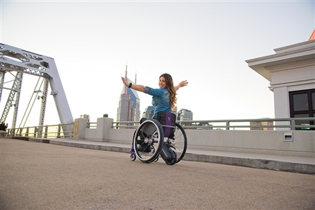 The SmartDrive MX2 pushing a wheelchair up a hill.