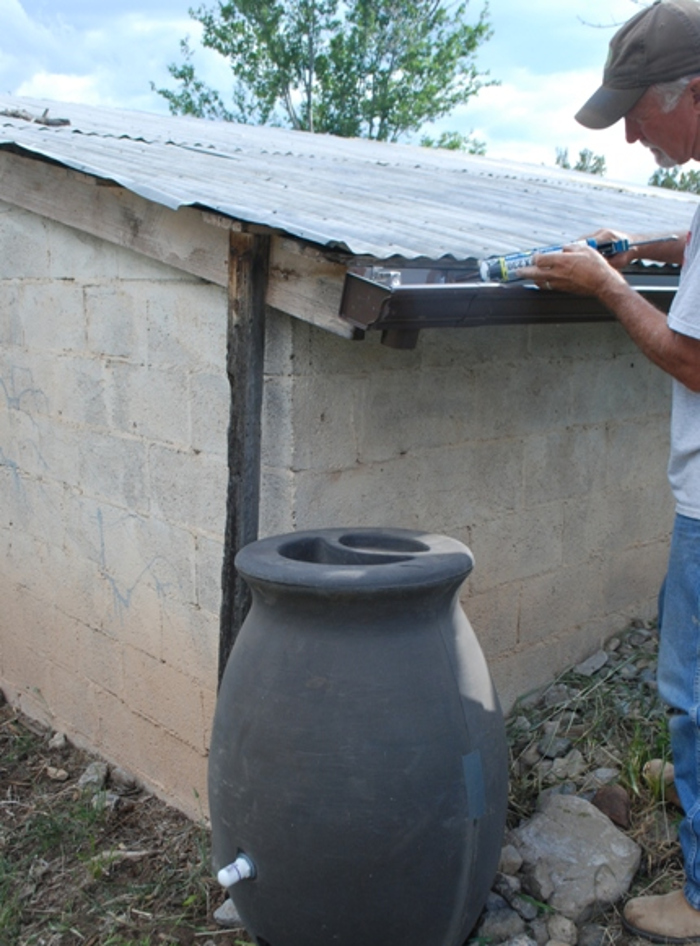 installed-a-new-rain-barrel-system-on-the-shed-near-a-vegetable-garden.jpg