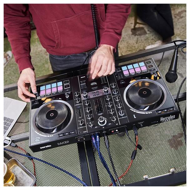 Man wearing red shirt using Hercules DJControl Inpulse 500 2-Channel DJ Controller