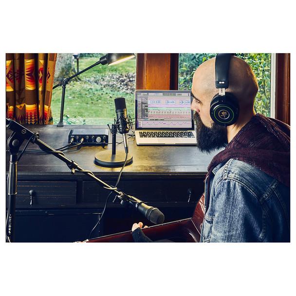 Person using MACKIE Producer Bundle: Onyx Producer interface, EM89D dynamic mic, EM91C condenser mic and MC-100 headphones.