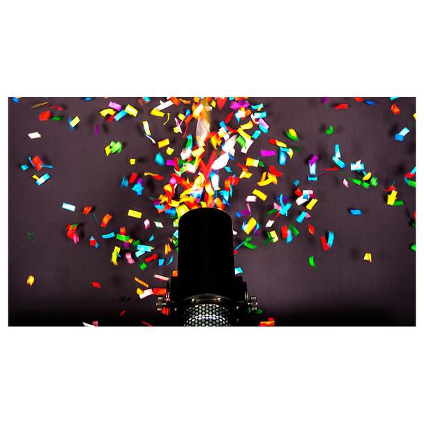 Action shot of CHAUVET Funfetti Shot event-ready confetti launcher shooting rainbow confetti onto black wall