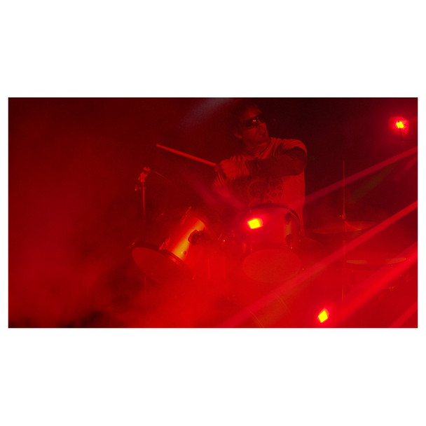 man playing drum set surrounded by red lights and fog created by Hurricane 1600