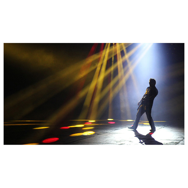 man standing on black ground with yellow and red lights shining on floor and fog created by Hurricane 1800 Flex