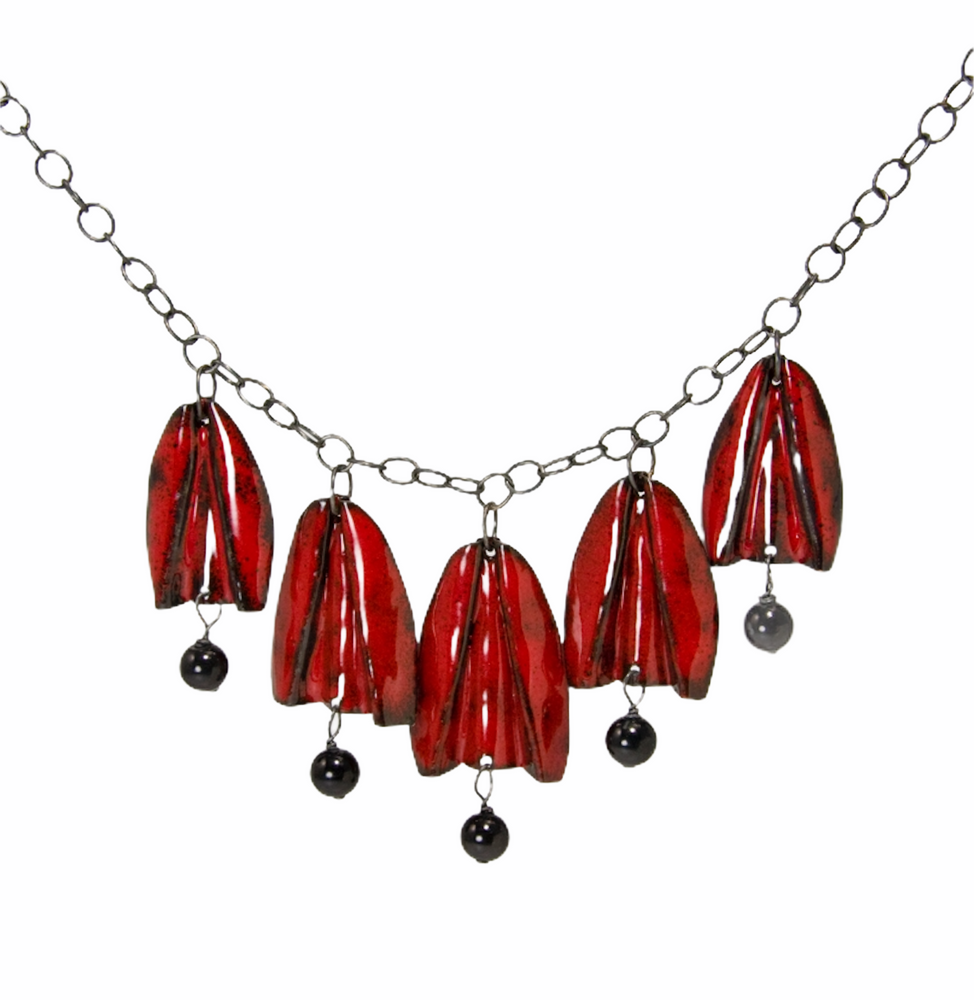 Red and gold enamel tulip flowers with black onyx drops hang from an oxidized sterling silver chain