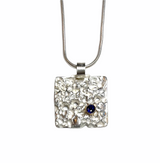 Textured sterling silver pendant with blue sapphire set in 14k gold