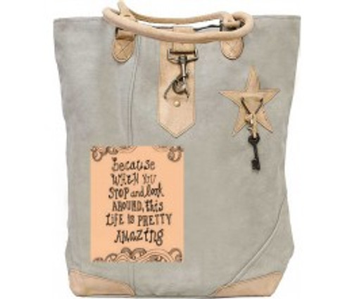 This tote is made from recycled tent canvas with a colorful patch, decorative key, metal clasp and  leather handles long enough to carry over your shoulder.