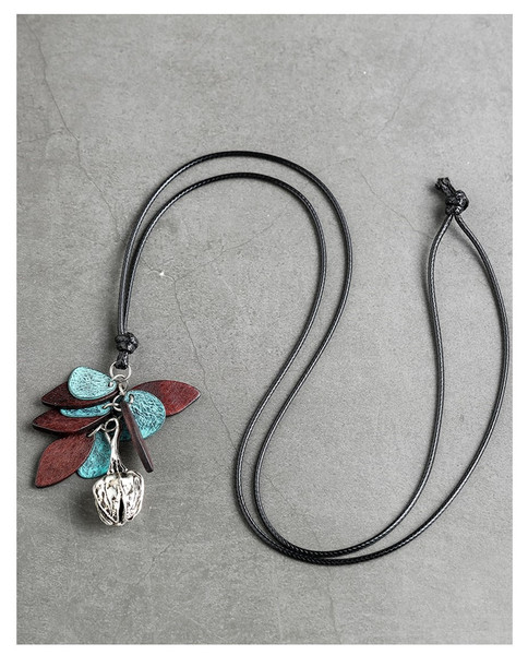 long cord pendant with wood and metal leaf shapes suspended beneath